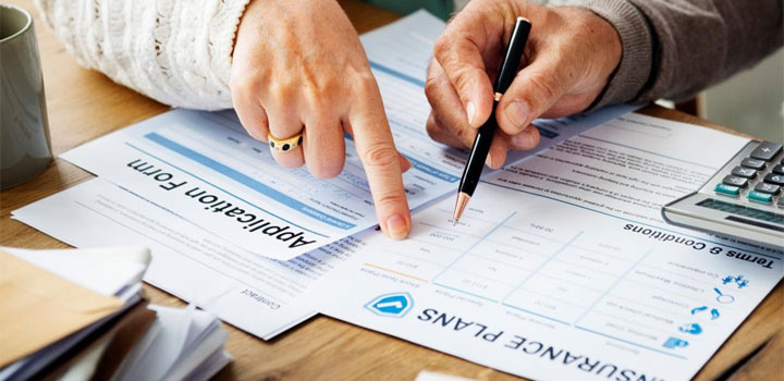 Man and woman signing insurance documents