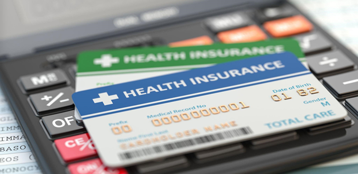 Two health insurance cards sitting on top of a calculator